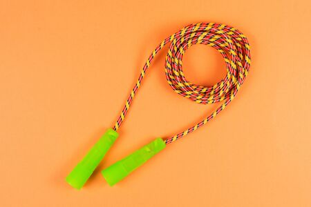 Jump rope on an orange background. Top view.