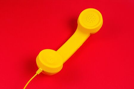 Yellow handset on red background. Copy space.
