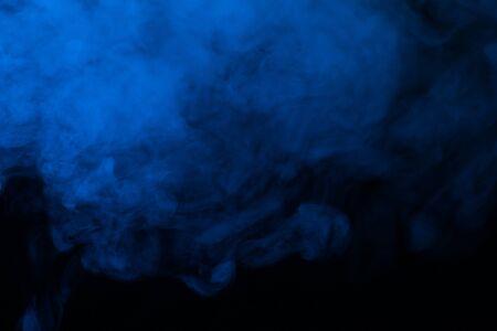 Vapeur bleue sur fond noir. Espace de copie. Banque d'images