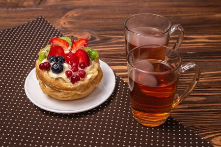 Home made cake with cream and fruit and hot tea on wooden background.  Banco de Imagens