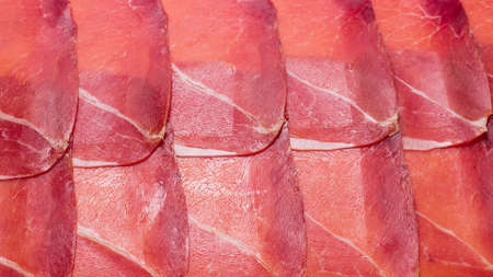 Tasty meat background, thinly sliced jamon. Top view.