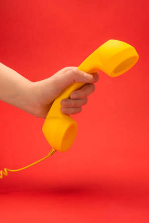 Yellow handset on a red background in woman hand. Copy space.