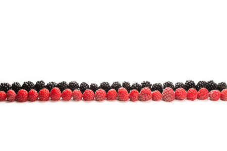 Raspberries and blackberry in a row isolated on white background. 免版税图像