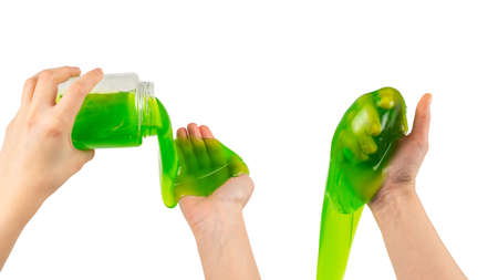 Green slime toy in woman hand isolated on white. Top view.