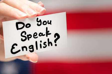 Do you speak English text on a card. American flag background.