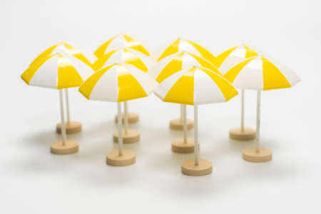 Yellow umbrellas on a white background. Copy space.