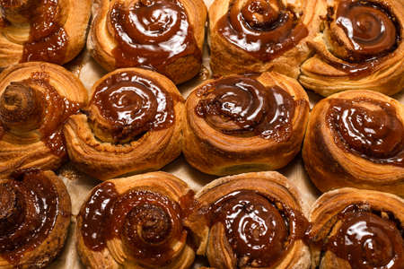 Homemade cinnamon buns with spices and caramel on parchment paper.