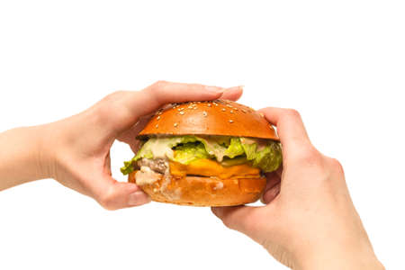 Hamburger in woman hands isolated on a white background. Top view.