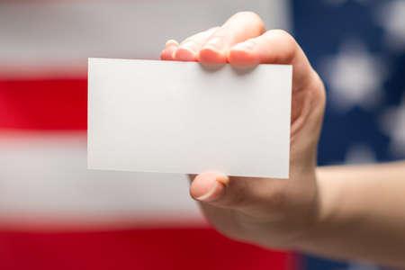 Empty card in woman hand. Copy space. American flag background. Foto de archivo