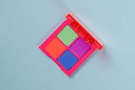 Purple, green, orange and blue eye shadow palette isolated on a blue background. Make up. Neon colors. Standard-Bild