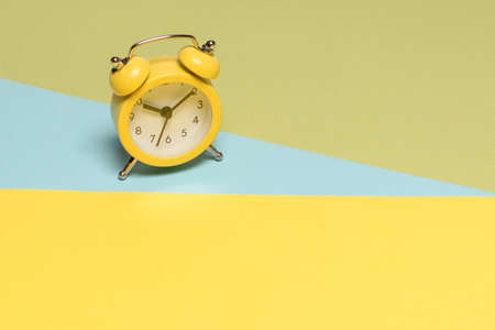 Yellow alarm clock on a yellow, blue and green background. Copy space. Time concept.