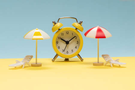 Time to travel. Sun lounger, yellow umbrella and alarm clock on a yellow, blue background. Standard-Bild