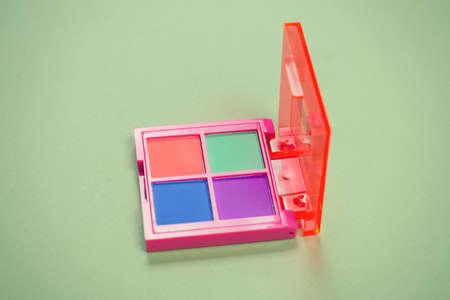 Purple, green, orange and blue eye shadow palette on a green background. Make up. Neon colors.