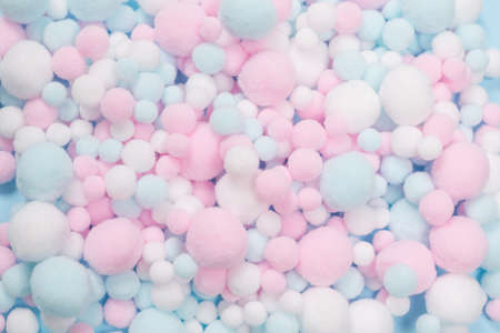 White, pink and blue soft pompons as a background. Bright background. Standard-Bild
