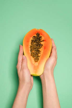 Papaya fruit on a green background in woman hands. Tropical fruit. Half papaya. Imagens