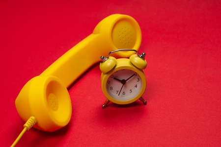 Time to call. Yellow handset and alarm clock on a red background. Copy space. Imagens