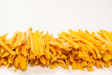 Dry tasty mango slices as a background. Top view. Imagens