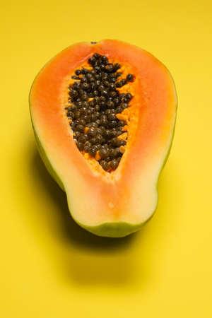 Papaya fruit on a yellow background. Tropical fruit. Half papaya. Imagens