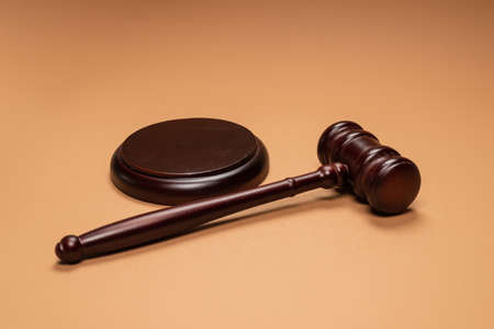 Gavel down on stand on brown background. Justice of law system conceptual. Copy space. Imagens