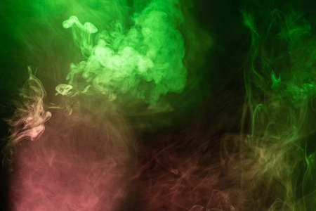 Green and pink steam on a black background. Copy space. Imagens