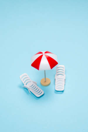 Travel concept. Sun lounger, red umbrella on a blue background. Copy space. Imagens