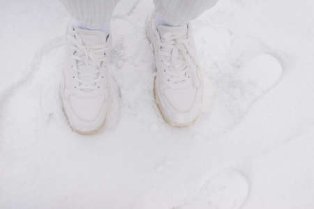 Woman in white pants and white sneakers stands in a snow.