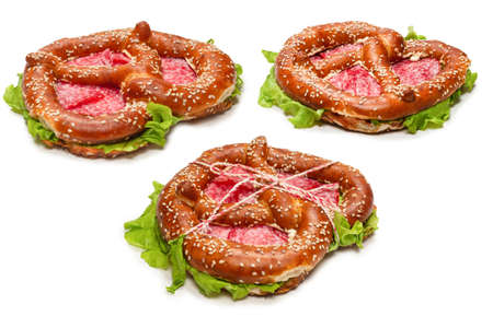 Pretzel with salami and lettuce isolated on a white background. Tasty snack.