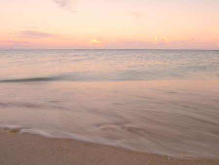 Beautiful sunset on a beach. Summer sunset and sea waves. Imagens