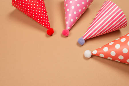 Colorful birthday cap on brown background. Copy space.
