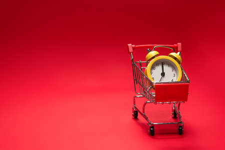 Shopping time. Yellow alarm clock in shopping basket on a red background. Copy space.