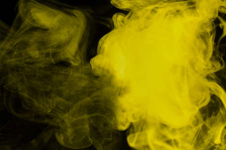 Yellow steam on a black background. Copy space.