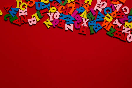 Random colorful alphabet on a red background, colorful letters. Top view. Imagens