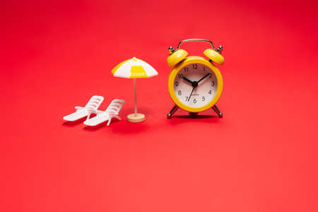 Time to travel. Sun lounger, umbrella and alarm clock on a red background.