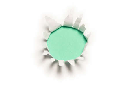 A hole in a white paper on a green background, copy space.