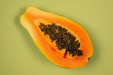 Papaya fruit on a green background. Tropical fruit. Half papaya. Imagens
