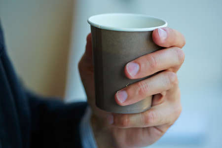 unrecognisable people: men with cup of coffee
