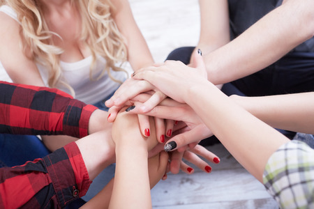 support group: group of students in a bright room on the floor sit in a circle holding hands