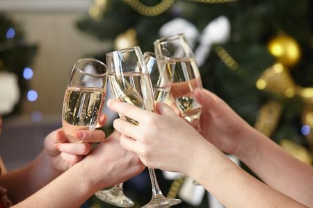 fiesta familiar: Copas de champán en manos femeninas en la fiesta de Navidad