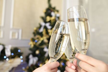 Glasses of champagne in female hands on Christmas party