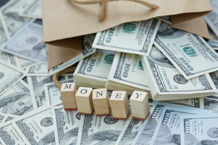 mucho dinero: Bloques de madera - el dinero de inscripción. una gran cantidad de dinero de una bolsa de papel Foto de archivo