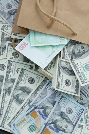 mucho dinero: una gran cantidad de dinero de una bolsa de papel. dólares y euros