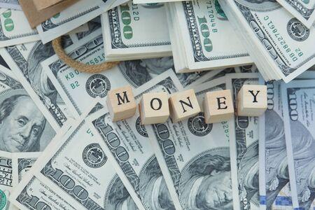 mucho dinero: Bloques de madera - el dinero de inscripci�n. una gran cantidad de dinero de una bolsa de papel Foto de archivo