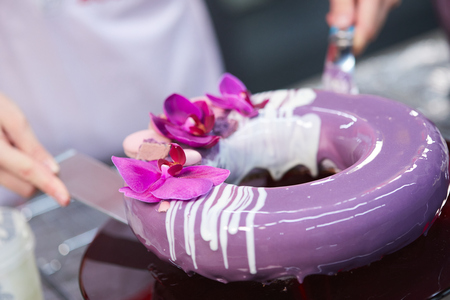 The chef covers the purple cake with icing