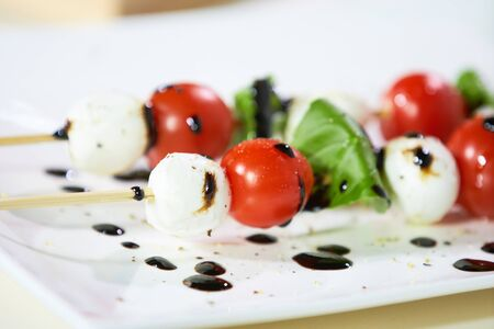 appetizer of cherry tomatoes, mozzarella, basil and sauce Stock Photo