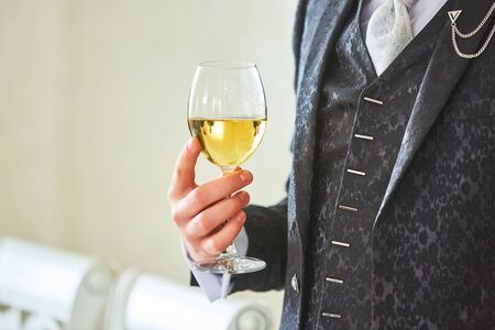 A glass of wine in a mans hand in a retro suit