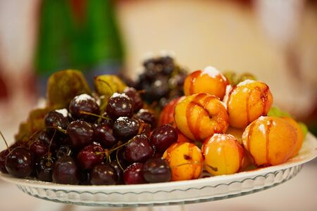 tasty fruit on a plate with pears, grapes, apricots
