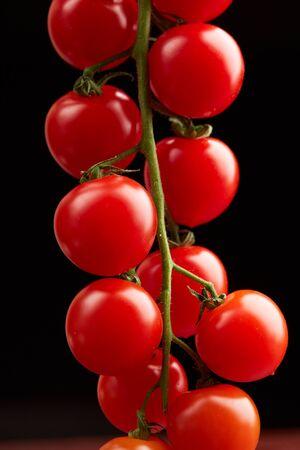Pomodori di ciliegia su sfondo nero Archivio Fotografico - 82921384