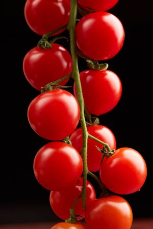 cherry tomatoes on a black background Foto de archivo