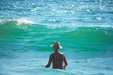 Woman with hat in the sea Banco de Imagens