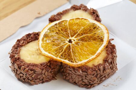 raw foodists dessert with banana, orange, seeds